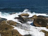 ocean water crashing on the rocky shore